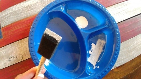 Loading foam brush with white paint.