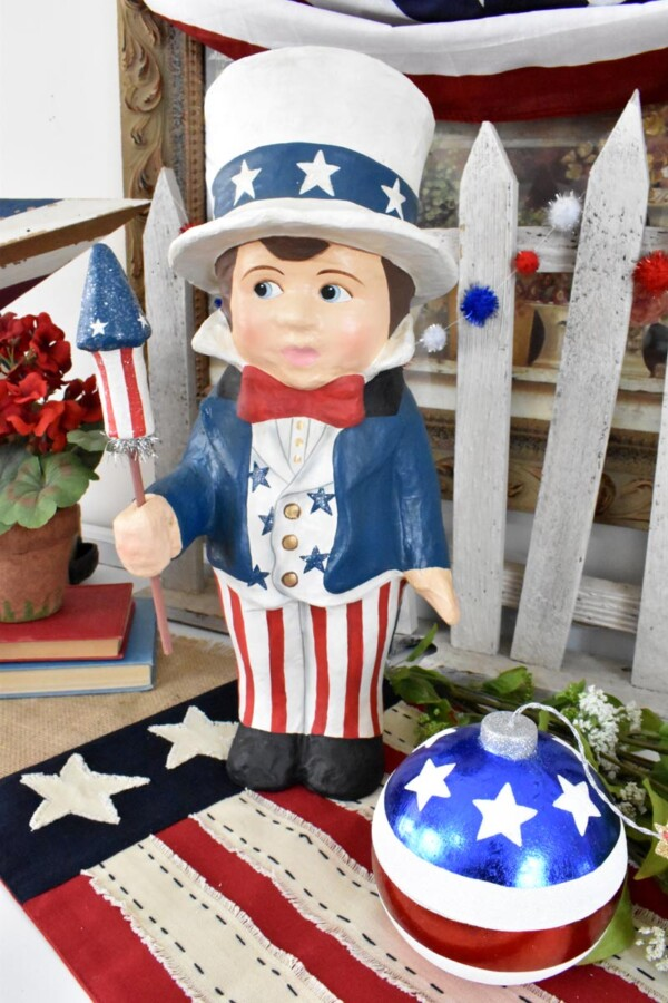 Close up of Sammy with firecracker in foreground and picket fence in background. Sammys Star Spangled Banner Vignette