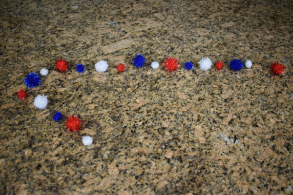 Red, White and Blue pom poms laying on table in order for DIY Patriotic Pom Pom Garland assembly.