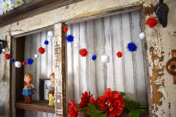 Right side view of vintage hutch withDIY Patriotic Pom Pom Garland draped twice across the top shelf.