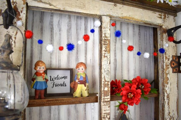 Left side view of DIY Patriotic Pom Pom Garland draped twice across the top shelf of decorated hutch.