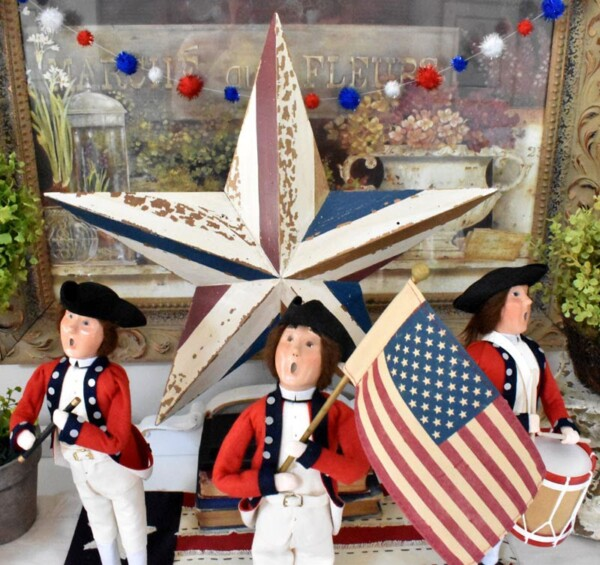 Fife and Drum Display with a DIY Patriotic Pom Pom Garland draped behind them across a picture. DIY Patriotic Pom Pom Garland