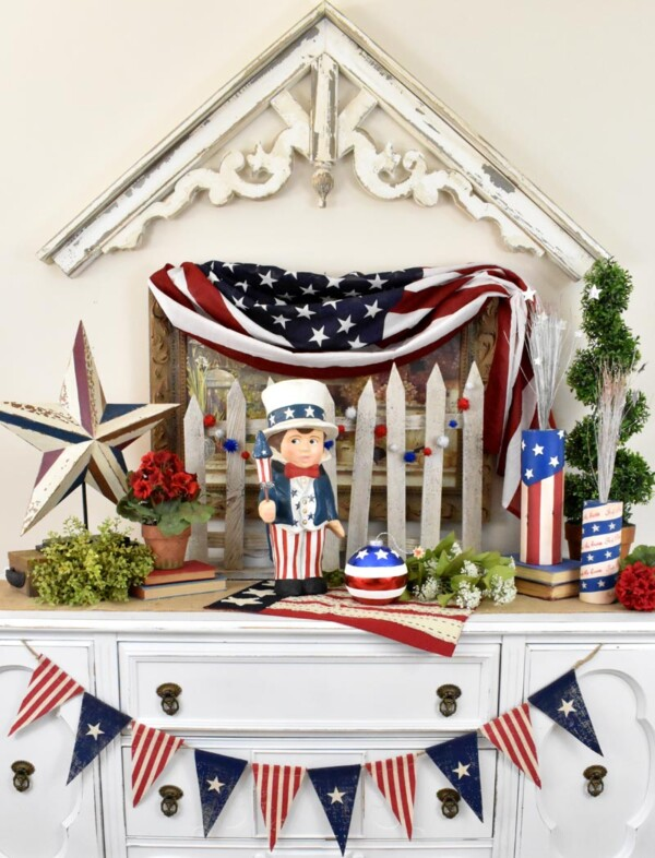 Sammys Star Spangled Banner - The paper mache figurine, Sammy, is standing in the middle of vignette on buffet.
