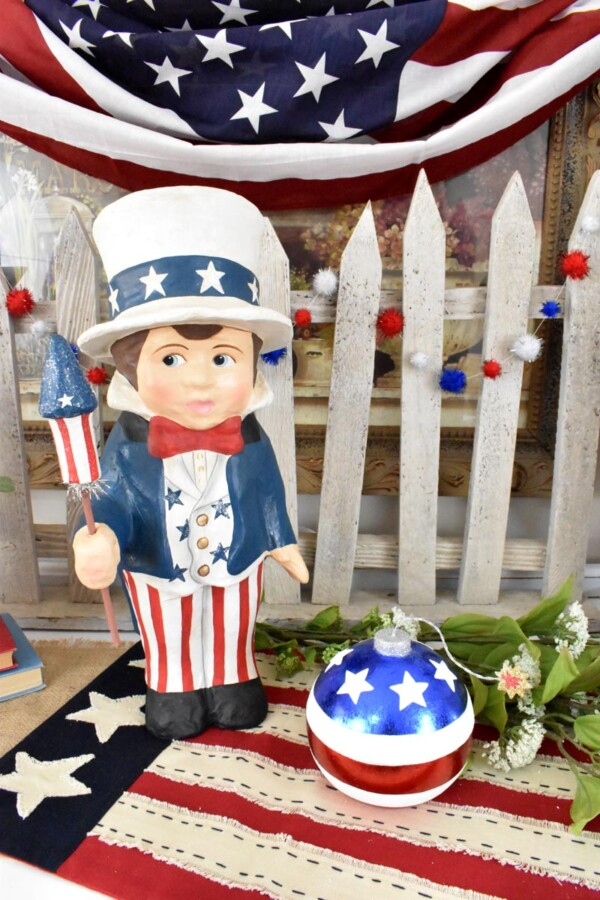 Sammy's Star Spangled Banner Display with DIY Patriotic Pom Pom Garland draped across a white picket fence behind him.